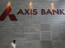 An employee speaks on his mobile phone as he walks inside Axis Bank's corporate headquarters in Mumbai