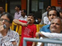 People look at a screen displaying the Sensex on the facade of the Bombay Stock Exchange (BSE) building in Mumbai