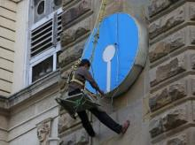 An electrician puts lights on the logo of State Bank of India at its main branch in Mumbai