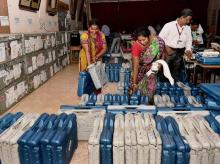 Polling officials check the EVM at a distribution centre