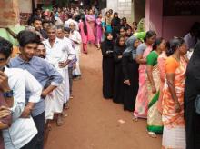 People wait to cast their votes for assembly elections at Puthurmadam in Kozhikode