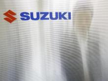 A man is seen through a compartment board with the logo of Suzuki Motor seen on it at the company's showroom in Tokyo