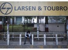 A man waits at a bus-stop with an advertisement of Larsen & Toubro outside the company's manufacturing unit