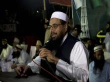 Hafiz Saeed, centre, chief of Pakistani religious group Jamaat-ud-Dawa an alliance of Islamic parties, addresses a gathering to condemn recent American drone attacks in Karachi, Pakistan