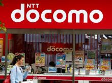 A woman walks past a brach of Japanese mobile communications company NTT Docomo in Tokyo, Japan. Photo: Reuters