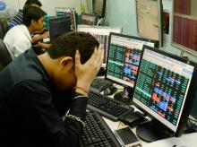 hare brokers react to falling stock prices on screens of computers and television