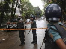 Bangladeshi policemen clear out an area to facilitate action against heavily armed militants who struck at the heart of Bangladesh's diplomatic zone on Friday night, taking dozens of hostages at a restaurant popular with foreigners in Dhaka.