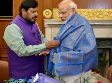Prime Minister Narendra Modi is presented a shawl by newly inducted minister Ramdas Athavale at a meeting in New Delhi