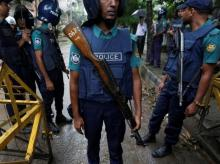 Policemen stand guard along a road leading to the Holey Artisan Bakery and the O'Kitchen Restaurant after gunmen attacked, in Dhaka