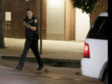 Dallas police move to detains a driver after several police officers were shot in downtown Dallas. Snipers apparently shot police officers during protests and some of the officers are dead, the city's police chief said in a statement.