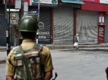 A CRPF man stand guards during restiction and srike on the fourth consuctive day in Srinagar. Photo: PTI