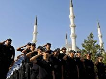 Turkish policemen salute as they attend a mass funeral for their comrades who were killed Friday during the failed military coup, in Ankara, Turkey