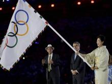 Tokyo Governor Yuriko Koike, right, waves the Olympic flag during the closing ceremony in the Maracana stadium.