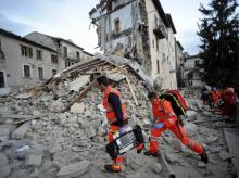 Rescuers search a crumbled building in Arcuata del Tronto, central Italy, where a 6.1 earthquake struck just after 3:30 am