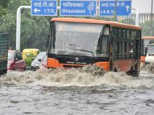 ehicle pass through water logged roads after rain in  New Delhi