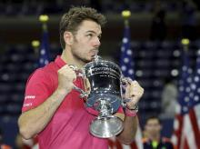 Stan Wawrinka of Switzerland, kisses the championship trophy after beating Novak Djokovic of Serbia, to win the men's singles final of the US Open tennis tournament in New York.