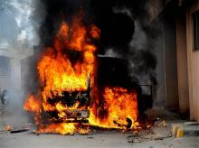 A vehicle from Tamil Nadu in flames after it was torched by pro-Kannada activists during a protest over Cauvery water row, in Bengaluru