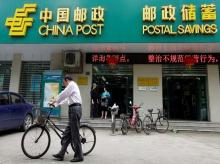 A man pushes his bicycle past a branch of China Post's Postal Savings Bank of China in Wuhan, Hubei province
