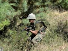 An army person takes position and moves towards the site where militants were hiding during an encounter at Lachipora in Uri Sector of north Kahsmir. Photo: PTI