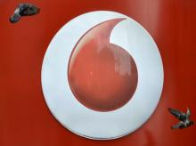 Pigeons fly past Vodafone branding outside a retail store in London. Photo: Reuters