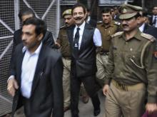 The Sahara group chairman Subrata Roy (C) is escorted by police to a court