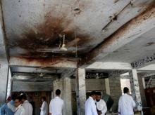 Men gather under a ceiling with blood stain, after twin bomb attack occurred at a court, in Mardan, Pakistan