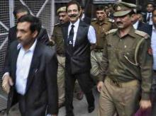 he Sahara group chairman Subrata Roy (C) is escorted by police to a court