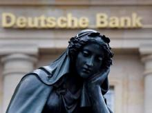 A statue is seen next to the logo of Germany's Deutsche Bank in Frankfurt, Germany. Photo: Reuters
