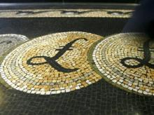 An employee is seen walking over a mosaic of pound sterling symbols set in the floor of the front hall of the Bank of England in London.  Photo: Reuters