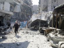 A civil defense member runs at a market hit by air strikes in Aleppo's rebel-held al-Fardous district.Photo: Reuters
