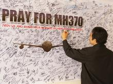 A man writes messages and prayers for Malaysia Airlines Boeing 777-200ER MH370 in IIUM Library, Kuantan Pahang, Malaysia. (Photo: Shutterstock)