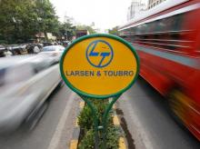 A sign of Larsen and Toubro (L&T) is placed on a road divider in Mumbai