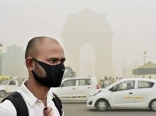 A man takes protection against pollution as smog covers India Gate in New Delhi on Sunday. (Photo: PTI)