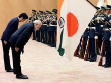 Indian Prime Minister Narendra Modi (2nd L) and his Japanese counterpart Shinzo Abe (L) bow to national flags as they review an honor guard before their meeting at Abe's official residence in Tokyo