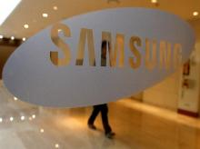 A man walks behind a logo of Samsung Electronics at the company's headquarters in Seoul. Photo: Reuters
