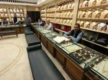 Sales persons wait for customers at a gold jewelry showroom in Chandigarh