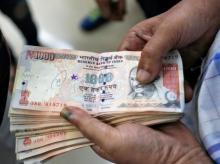 A customer waits to deposit 1000 Indian rupee banknotes in a cash deposit machine at bank in Mumbai