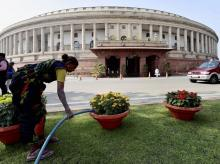 A gardner waters flower pots at Parliament House during the Winter Session, in New Delhi. Photo: PTI