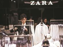 An employee arranges clothes at a Zara store, operated by Inditex SA, in Hong Kong, China