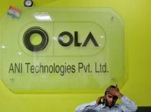 An employee speaks over his phone as he sits at the front desk inside the office of Ola cab service in Gurugram (Photo: Reuters)