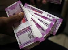A cashier displays the new 2000 Indian rupee banknotes inside a bank in Jammu (Photo: Reuters)