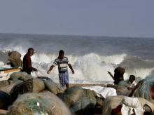 Fishermen stand near boats as waves break on the cost of the Bay of Bengal in Chennai on Thursday. Tropical Cyclone 'Nada' was forecast to strike on the southern coast. Photo: PTI