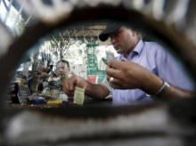 A man works inside the cash counter of a petrol station as people gather around to fill petrol for their vehicle in Kathmandu, Nepal. Photo: Reuters