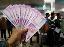 A bank officer in Jammu displays a bunch of new ~2000 notes, while customers queue up to withdraw cash. Photo: PTI