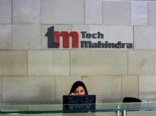 File photo of an employee sits at the front desk inside Tech Mahindra office building in Noida on the outskirts of New Delhi