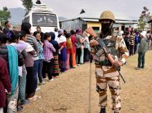 A security person stands guard as voters wait in a long queue to cast votes at a polling station during the last phase of assembly polls in Tengoupal, Manipur. Photo: PTI