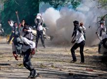 Student throwing stones on police amid heavy tear smoke during a clash with police outside SP college in the vicinity of Lal Chowk in Srinagar