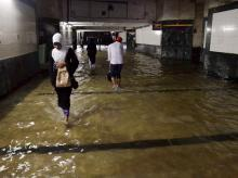 File photo: Commuters make their way through a flooded subway at Ghansoli Railway Station ater heavy downpour in Navi Mumbai. Photo: PTI