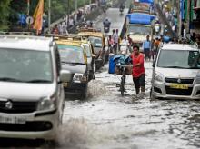 Vehicles plying at a waterlogged road after heavy rains, in Mumbai. Photo: PTI