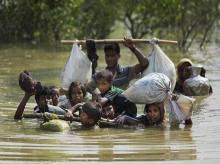A Rohingya family reaches the Bangladesh border after crossing a creek of the Naf river on the border with Myanmmar, in Cox's Bazar's Teknaf area. (File Photo: AP/PTI)